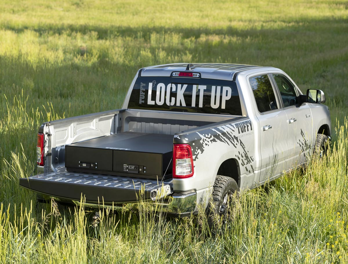 Tuffy security in tall grass field with lock box on the bed of the truck