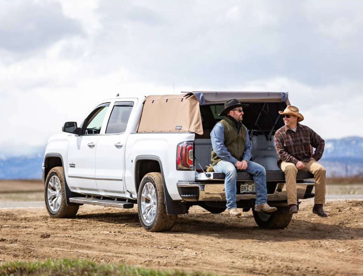 Softopper White GM truck with two ranchers talking sitting on the truck bed